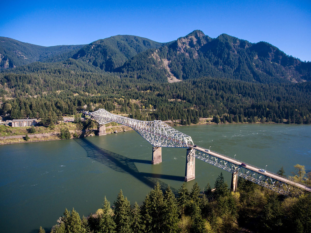 Arial photo of Bridge of the Gods over the Columbia River with coniferous trees and mountains in backgrounds
