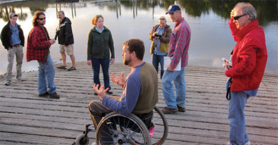 Mike Passo sitting in his manual wheel chair and speaking to a group of people standing on a wooden dock.