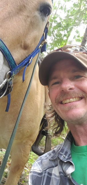 Smiling person with mustache and cap standing next to horse with trees in background