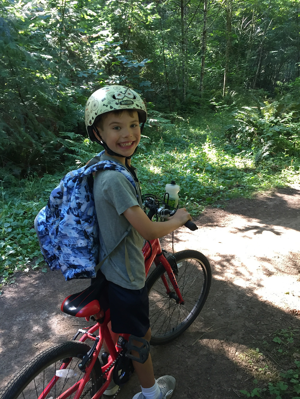 child with helmet and backpack straddling a bike and smiling on trail through forest