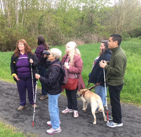 six people on a gravel path with grass and trees in background. Three people are holding white canes. One has a guide/support dog. One is using binoculars.