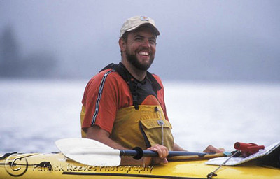White man smiling from yellow kayak