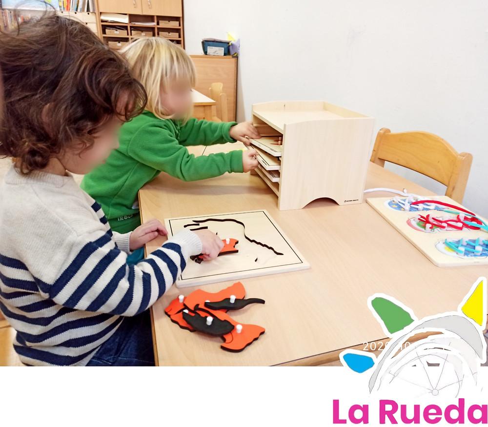 Niños interactuando con material montessori, puzzles y estanterías