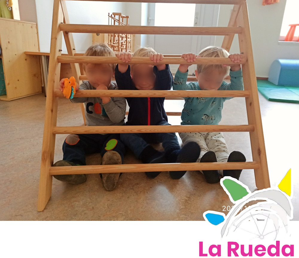 Niños jugando dentro del triángulo de Pikler