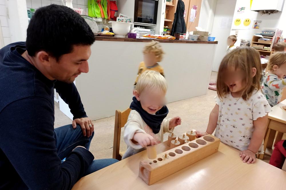 Niño jugando con material montessori en compañía de un pedagogo.