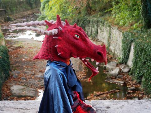 Enfant portant un masque intégral de dragon rouge en feutre artisanal
