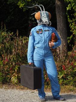 Femme costumée en cosmonaute et tête de mante alien, portant une poule et une valise