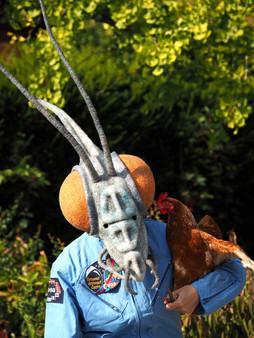 Femme costumée en cosmonaute et tête de mante alien, portant une poule qui semble lui faire un bisou