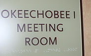 Photograph of a conference room sign givin room in braille.