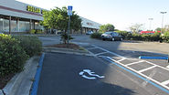 Photograph of an accessible parking space at a strip center.