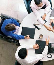 Overhead photograph of co-workers sitting at a round conference table and one person is sitting in wheelchair.