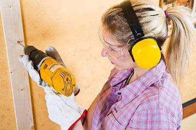 Female carpenter  at work using hand dri