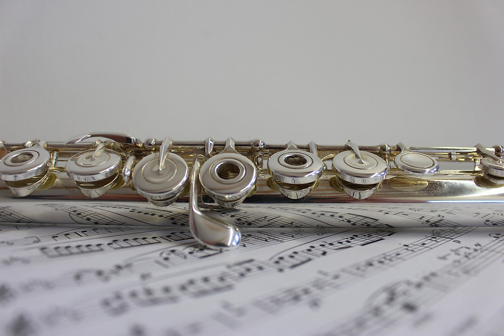 Flute on a page of sheet music, against a grey background