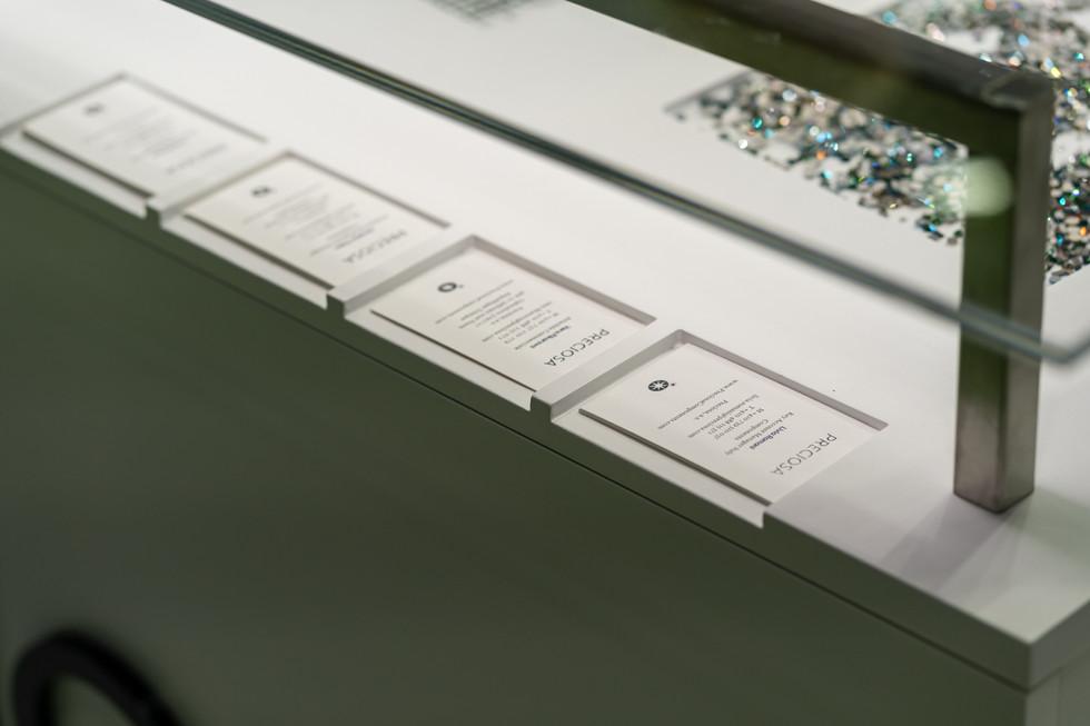 Prostor pro vizitky. Nerezový držák skla má zároveň zabudované osvětlení, které svítí na vzorky na pultu.