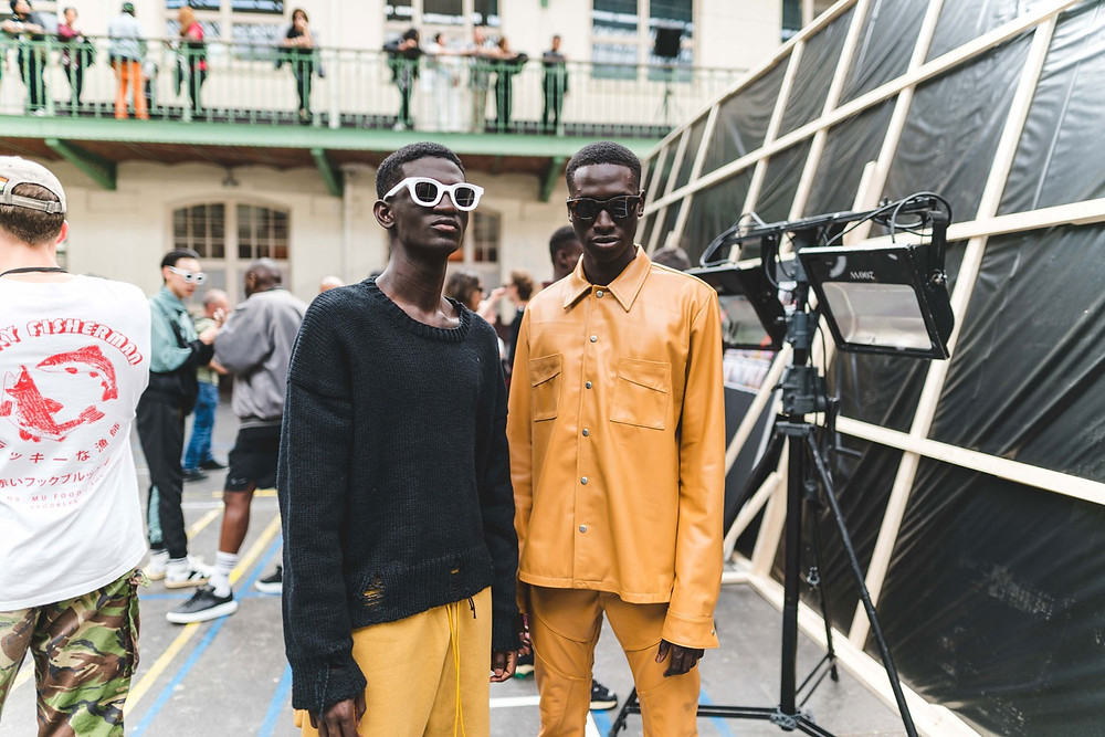 Two models wear Rhude pieces. On the left, a ripped, black sweater and mustard trousers; on the right, a golden-orange leather shirt and trousers
