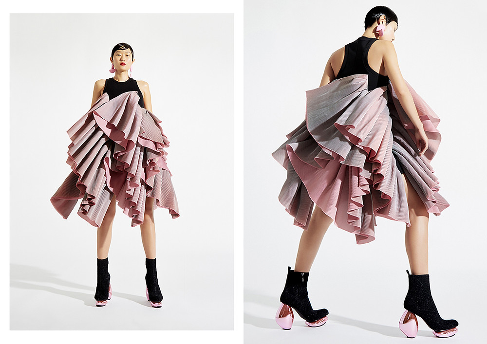 A model wears a black and pink, flowy design by Wun, also featuring several layers of fabric to create a dramatic skirt