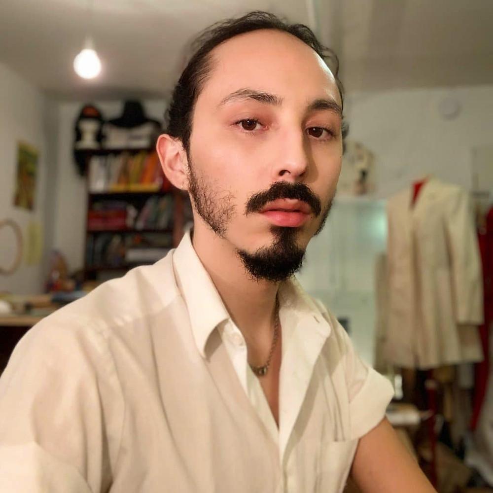 Evan Ducharme poses in studio while wearing white shirt