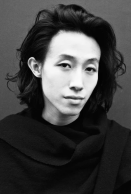 A black-and-white headshot of Wun from the chest up