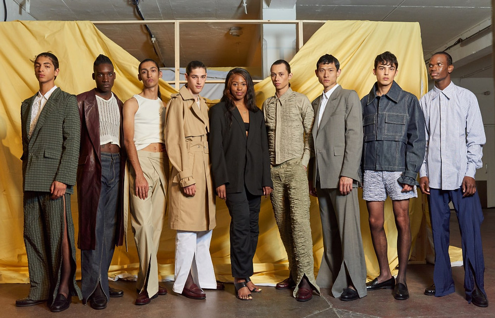 Designer Bianca Saunders stands center amongst a cast of models donning her menswear collection shown at London Fashion Week