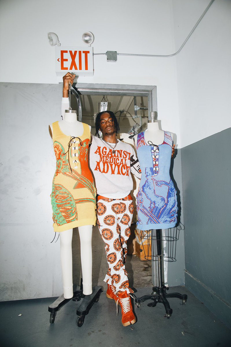 Olosunde poses with two mannequins fitted with skeleton-bearing dresses