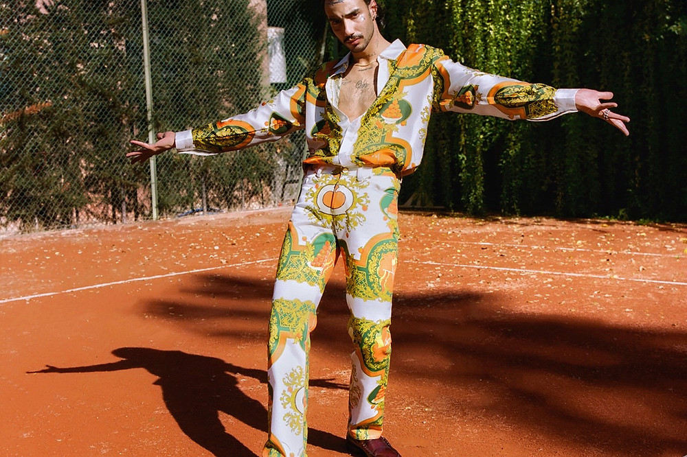 A model poses in Tajer's colorful designs; they wear matching, printed shirt and trouser
