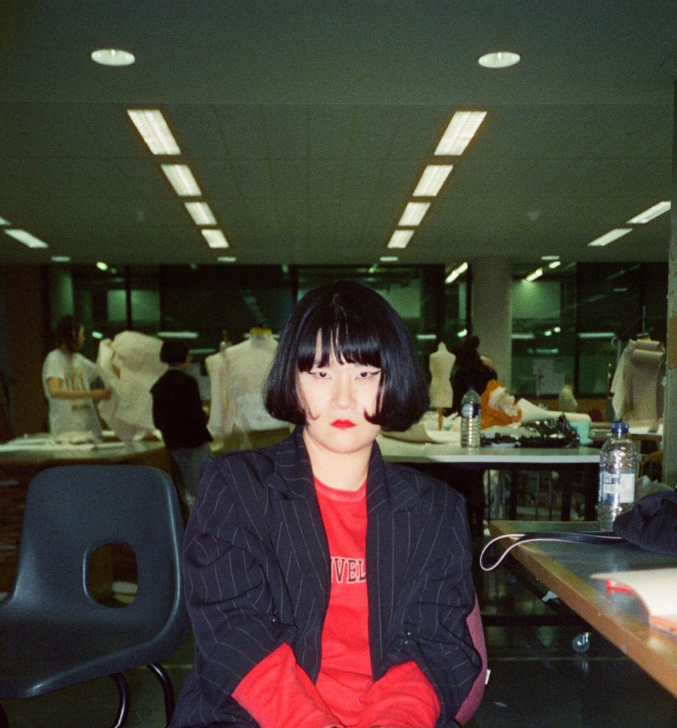 Goom Heo poses in a white blouse, navy blazer, and striking makeup.