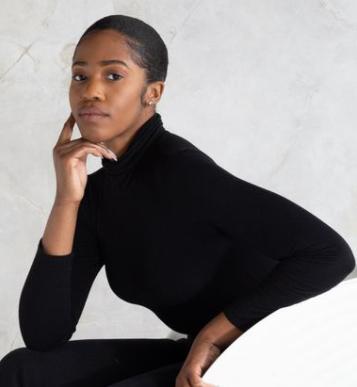 Bianca Saunder wears all black ensemble while sitting on white chair