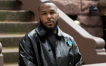 Jason Rembert poses in a black, leather jacker adorned with a blue broach