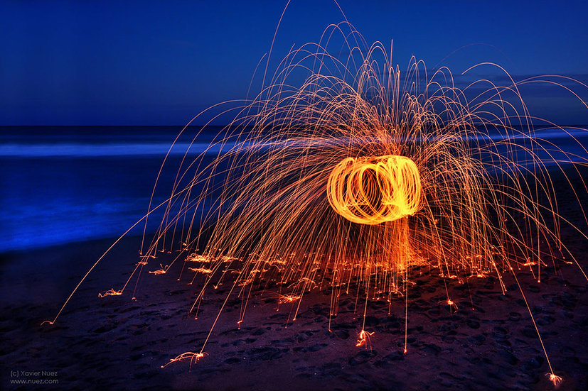 "A ""long exposure"" ""steel wool"" artwork of flying sparks on a beach at night by artist Xavier Nuez"