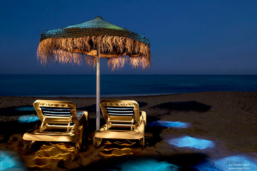 A beautiful, peaceful and relaxing view of beach chairs by the ocean at night with magical lighting