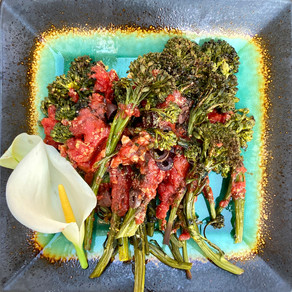 Roasted broccolini topped with tomatoes and olives