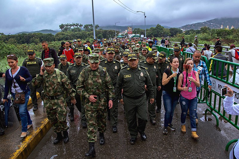 Colombian Police leading Venezuelan migrants accross the border to Cúcuta, Colombia. By Policia Nacional de Colombia [CC BY-SA 2.0  (https://creativecommons.org/licenses/by-sa/2.0)], via Wikimedia Commons.