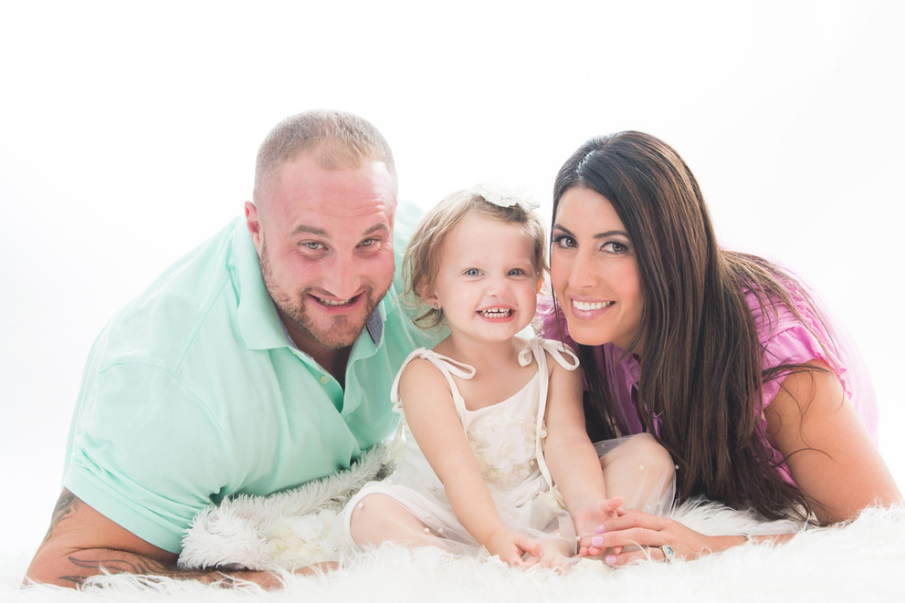 Happy family of three portrait taken inside Kelly Scky photography studio