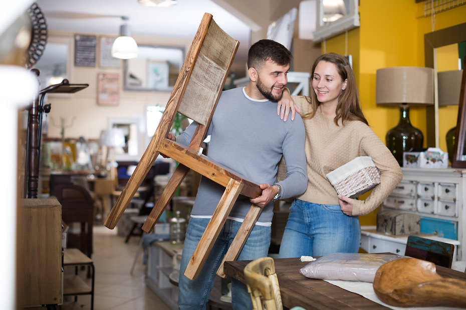 couple buying chair and basket at thrift store