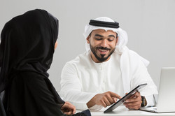 Arab businessman and businesswoman using