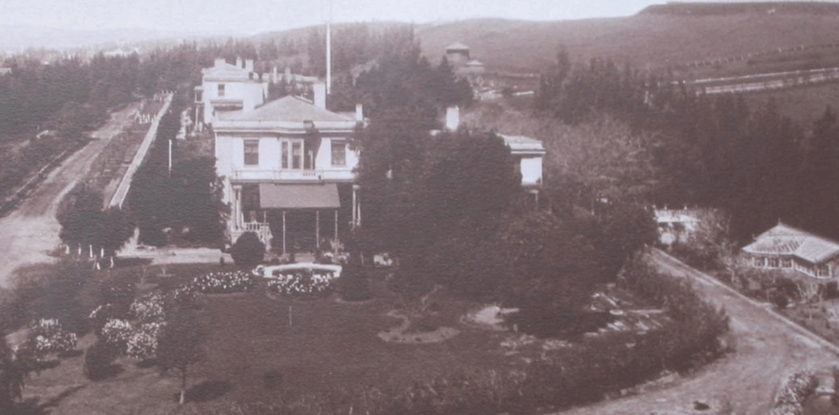 A past view across Officers' Row, with the lush garden and pool of the Commanding Officer's Quarters in the foreground.