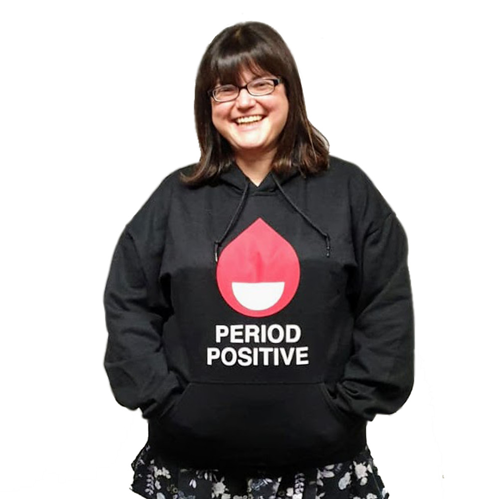 Chella is wearing a black hoodie with the Period Positive logo, which is blood drop and a smiley face