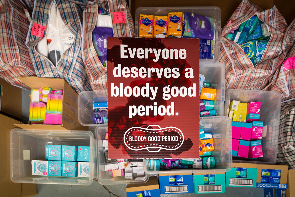 A BGP placard reading 'Everyone deserves a bloody good period' lying across boxes of menstrual supplies at BGP's storage unit