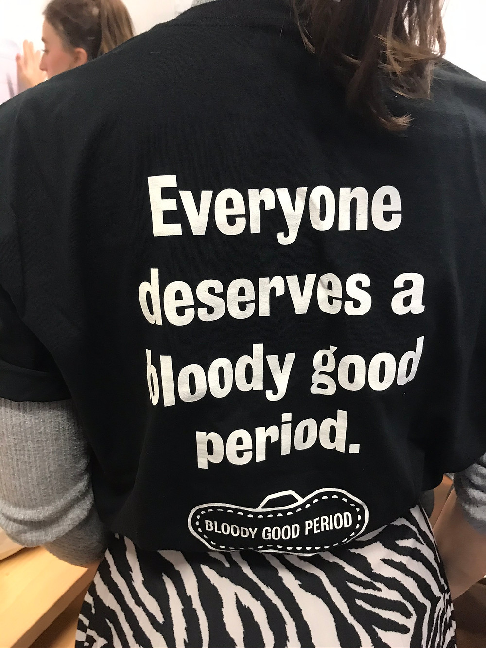 Woman wearing a T-shirt which reads 'Everyone deserves a bloody good period'