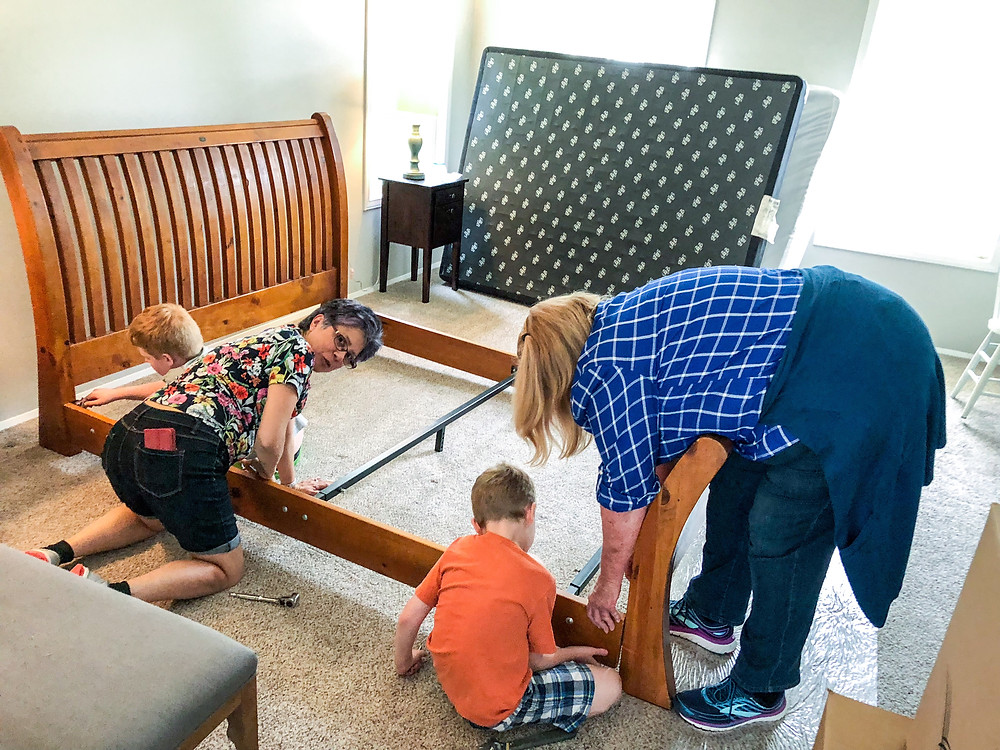 grandmas and kids setting up the bed