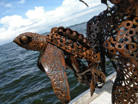"Sea turtle made from chains and old pipe, held in hands of ""Heart of Water"" sculpture"