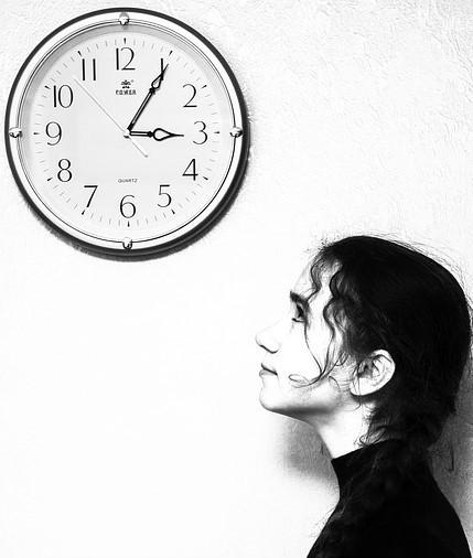 Uma mulher olhando fixamente no relógio, ansiosa com o futuro