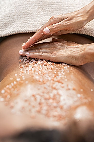 Closeup of masseuse woman applying scrub