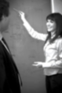 consultant pointing to a flowchart on whiteboard