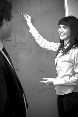 Image of a consultant pointing to a flow chart on a whiteboard