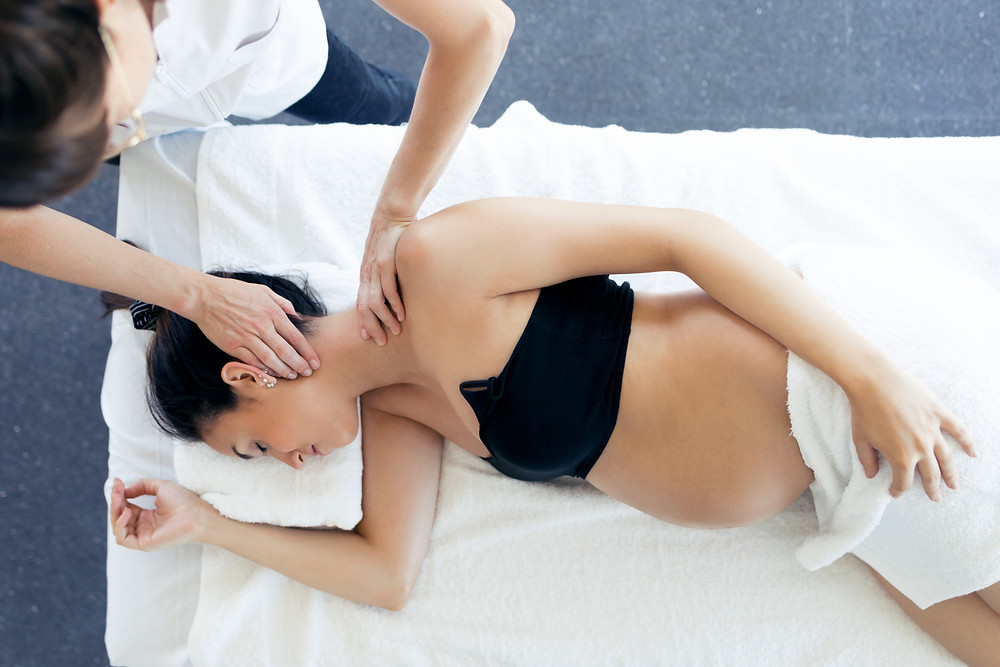 A pregnant woman is lying on a table while a Chiropractic massages her neck.