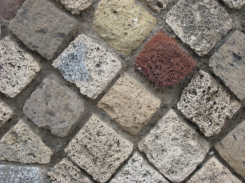 Photo of multi colored stones in a wall.