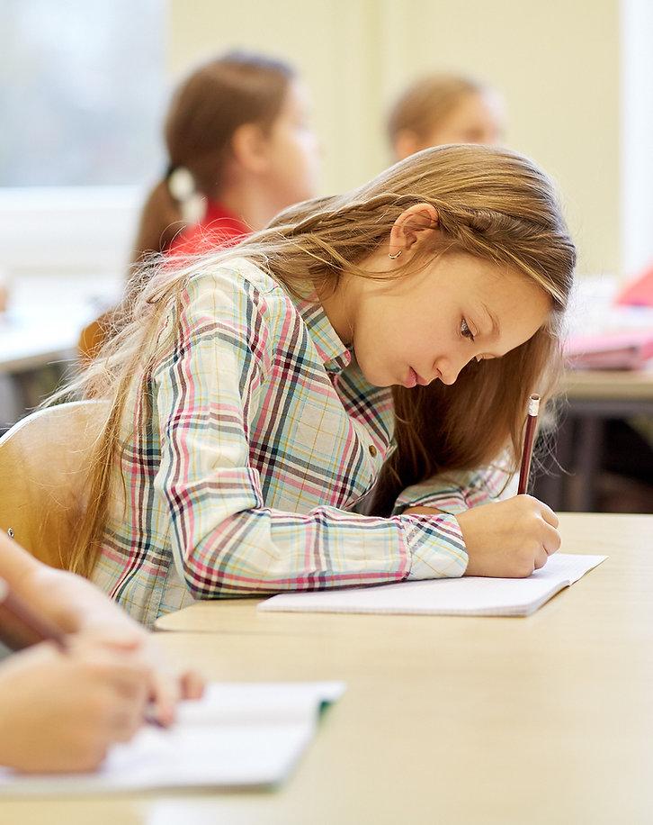 Fotografia szkolna, uczennica pisze sprawdzan. widać skupienie na jej twarzy. Oferta dla szkół
