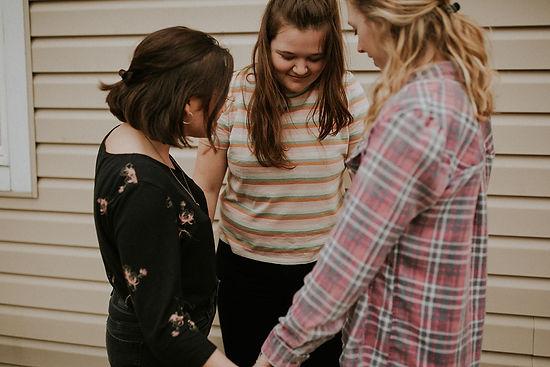 women circled up praying together