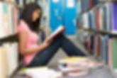 female-student-sitting-on-library-floor-
